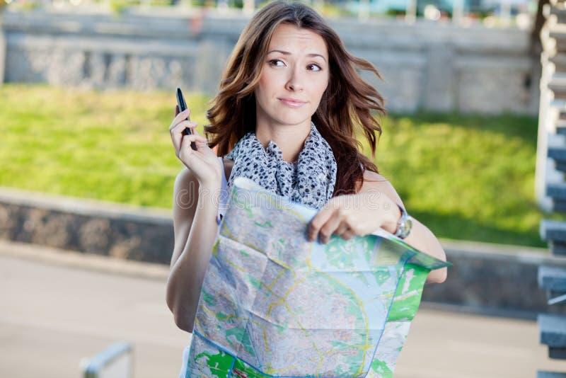 Turista da jovem mulher que guardara o mapa de papel fotografia de stock