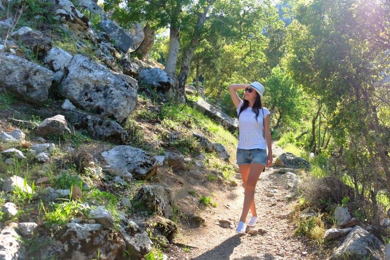 Turista da mo?a em um chap?u em uma caminhada em uma estrada de floresta da montanha, nas ru?nas da cidade antiga Termessos nos r fotos de stock royalty free