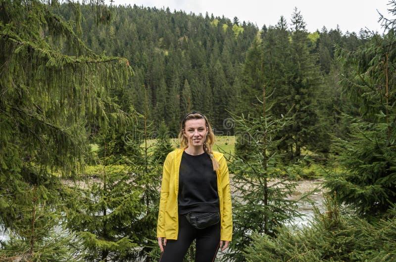 Turista da moça no fundo das montanhas, da floresta conífera e do rio da montanha durante uma viagem aos Carpathians imagens de stock royalty free