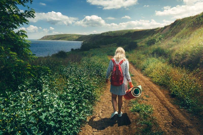 Turista da moça, vista de atrás, andando ao longo da estrada para o conceito do mar da caminhada e da aventura imagens de stock