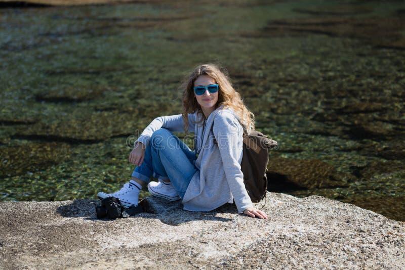 Turista da mulher com assento da câmera e da trouxa e relaxamento foto de stock