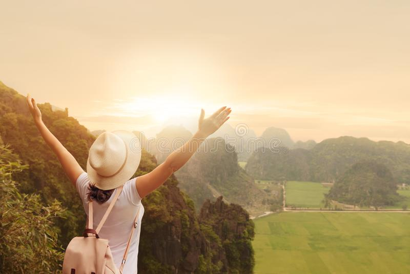 Turista da mulher com trouxa que aprecia a opinião do vale com braços acima da parte superior de uma montanha com por do sol imagem de stock royalty free