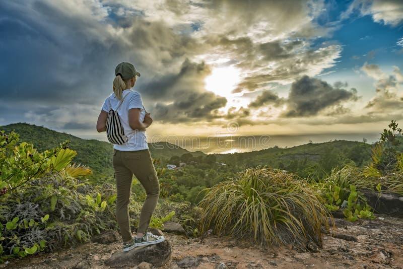 Turista da mulher no auge da montanha no por do sol fora durante uma caminhada no verão O viajante da menina com uma trouxa admir foto de stock