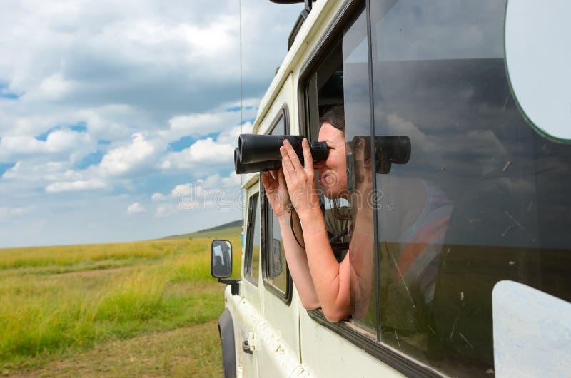 Turista da mulher no safari em África, curso em Kenya, animais selvagens de observação no savana com binóculos imagens de stock royalty free