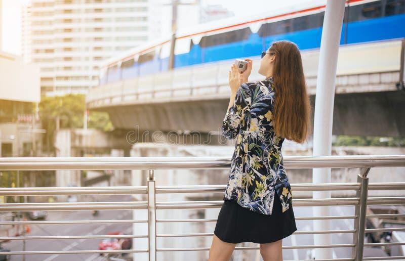 Turista da mulher que anda no centro de Banguecoque e que toma a foto com câmara digital fotografia de stock royalty free