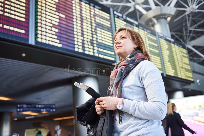 Turista da mulher que está no aeroporto no fundo das partidas imagens de stock