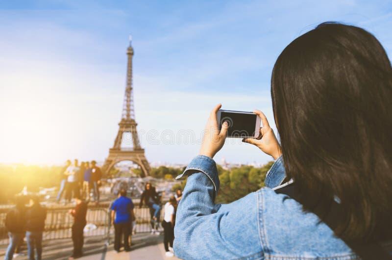 Turista da mulher que toma a foto pelo telefone perto da torre Eiffel em Paris sob a luz solar e o céu azul Turístico popular fam fotos de stock royalty free