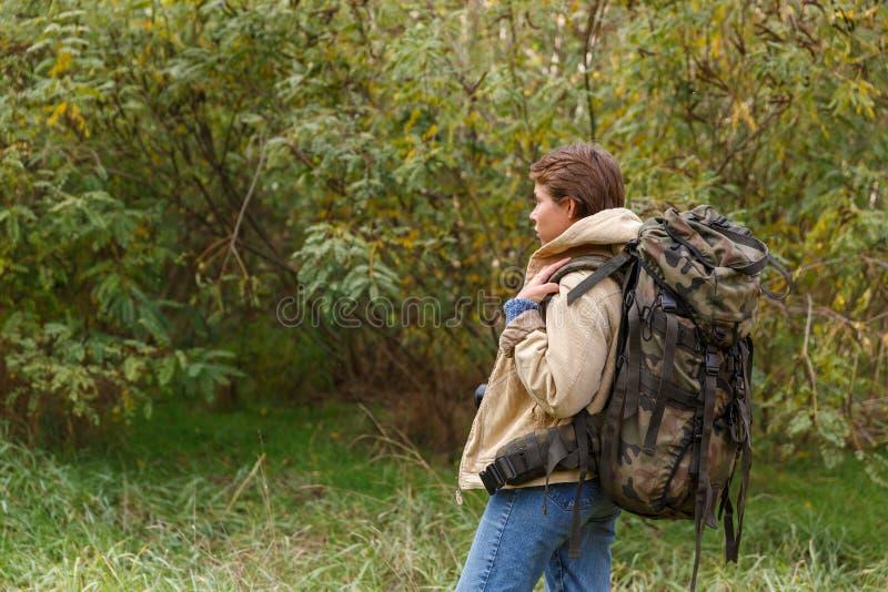 Turista de la chica joven, caminando a través de un bosque con una mochila grande en ella detrás fotos de archivo libres de regalías