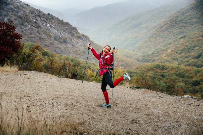 Turista de la chica joven con los bastones que engañan alrededor en un rastro de montaña en lluvia foto de archivo