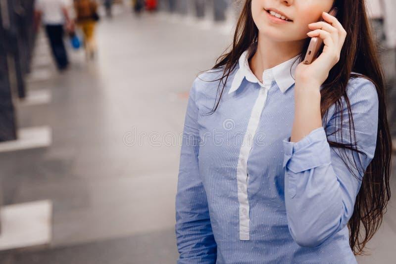 Turista de la chica joven que habla en el teléfono en el subterráneo y la sonrisa imágenes de archivo libres de regalías