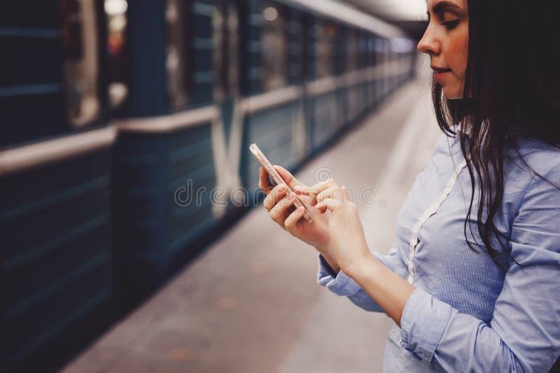 Turista de la chica joven que habla en el teléfono en el subterráneo y la sonrisa imagen de archivo