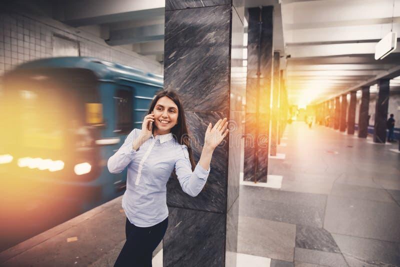 Turista de la chica joven que habla en el teléfono en el subterráneo y la sonrisa imagenes de archivo