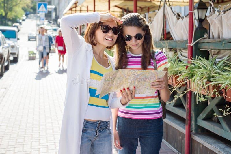 Turista de la mamá y de la hija que mira el mapa en la calle de la ciudad europea, viaje a Europa fotografía de archivo libre de regalías