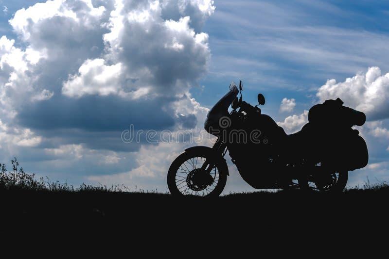Turista de la motocicleta del camino con los bolsos laterales, jinete a descansar durante el viaje para ver la luz de la naturale fotografía de archivo
