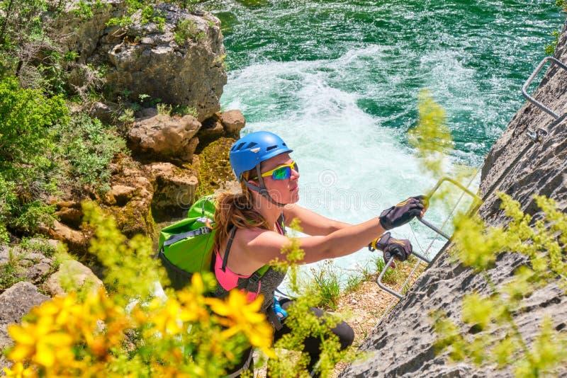 Turista de la mujer, con el engranaje que sube, ascendiendo en vía la ruta del ferrata en el barranco de Cikola, Croacia, en un d imágenes de archivo libres de regalías
