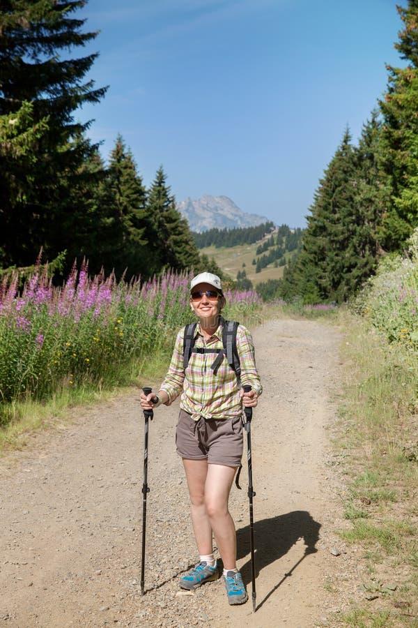 Turista de la mujer con la mochila en el camino imágenes de archivo libres de regalías