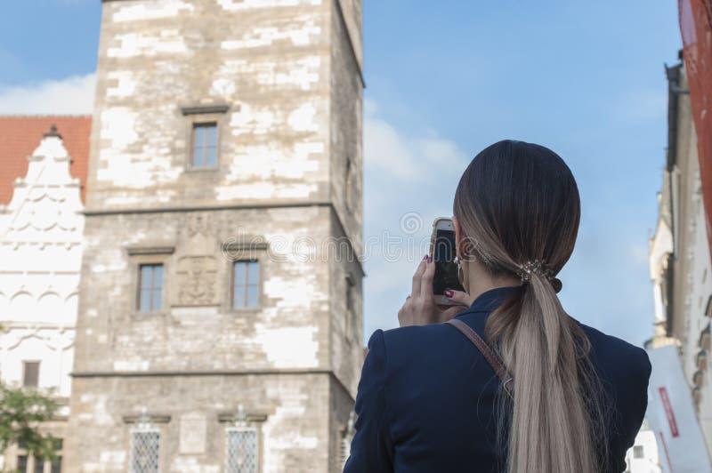 Turista de la mujer con su cámara del teléfono en las manos que tiran en Praga foto de archivo libre de regalías