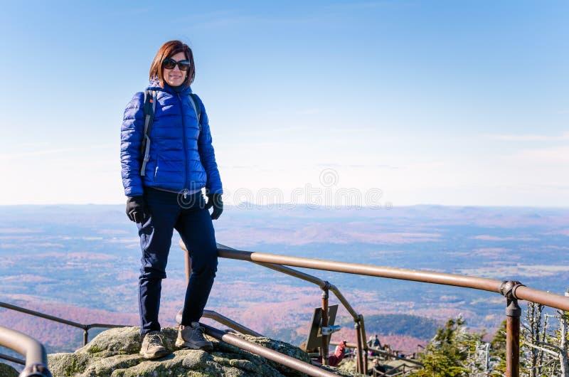 Turista de la mujer en el pico de una montaña y de un cielo azul imagenes de archivo
