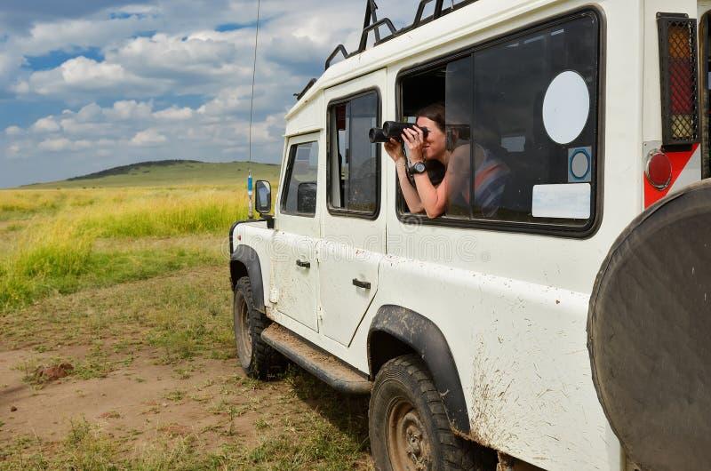 Turista de la mujer en el safari en África, viaje en Kenia, fauna de observación en sabana con los prismáticos imagen de archivo libre de regalías