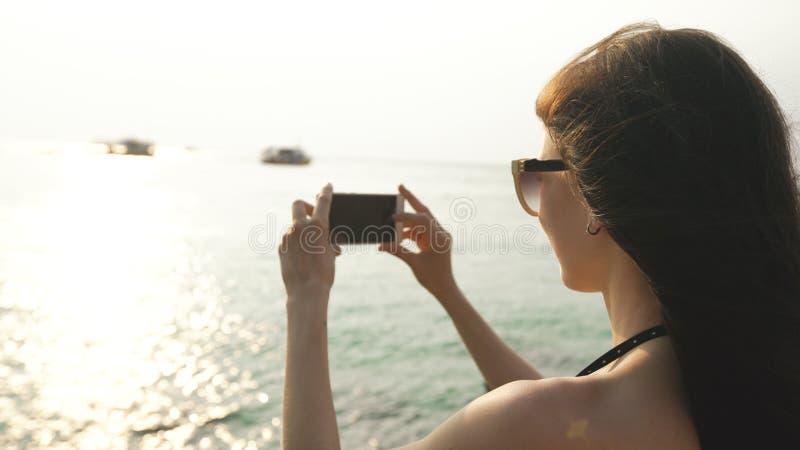 Turista de la mujer en la isla de la playa que toma la fotografía de la puesta del sol con smartphone el día de fiesta del barco  imagenes de archivo
