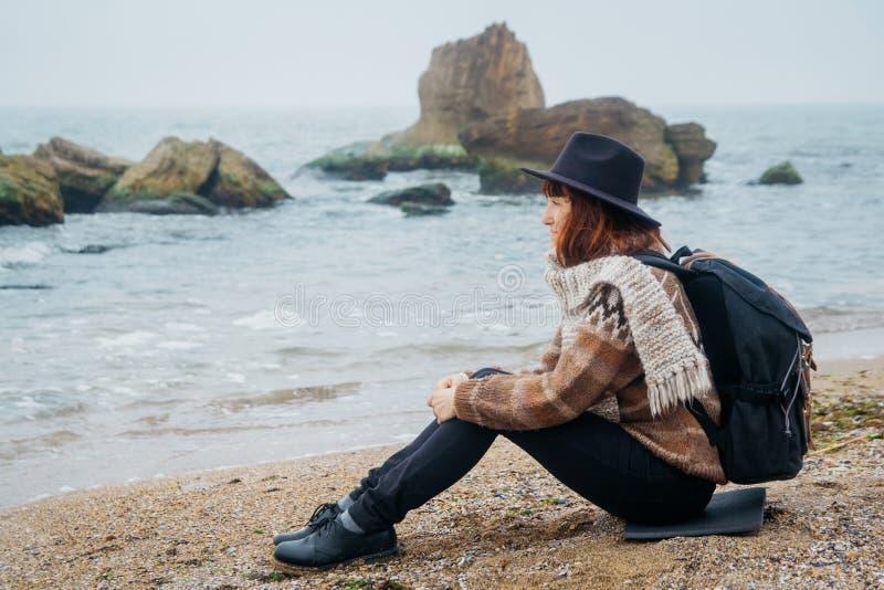 Turista de la mujer joven en sombrero y con la mochila que se sienta en la playa, mirando el mar, en la costa costa, en horizonte imagenes de archivo
