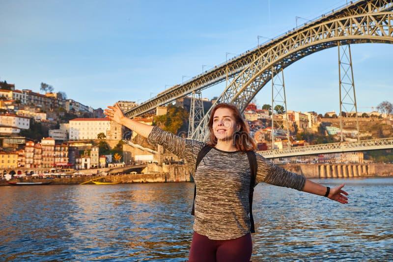 Turista de la mujer joven que disfruta de la opinión hermosa del paisaje sobre la ciudad vieja con el río y el puente famoso Dom  foto de archivo