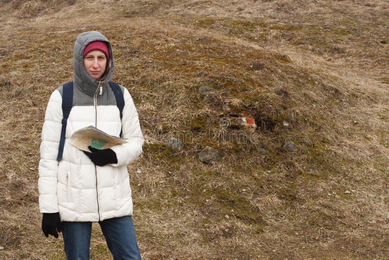 Turista de la mujer joven que mira el mapa en el fondo del parque nacional foto de archivo libre de regalías