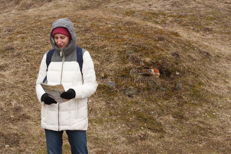 Turista de la mujer joven que mira el mapa en el fondo del parque nacional imágenes de archivo libres de regalías