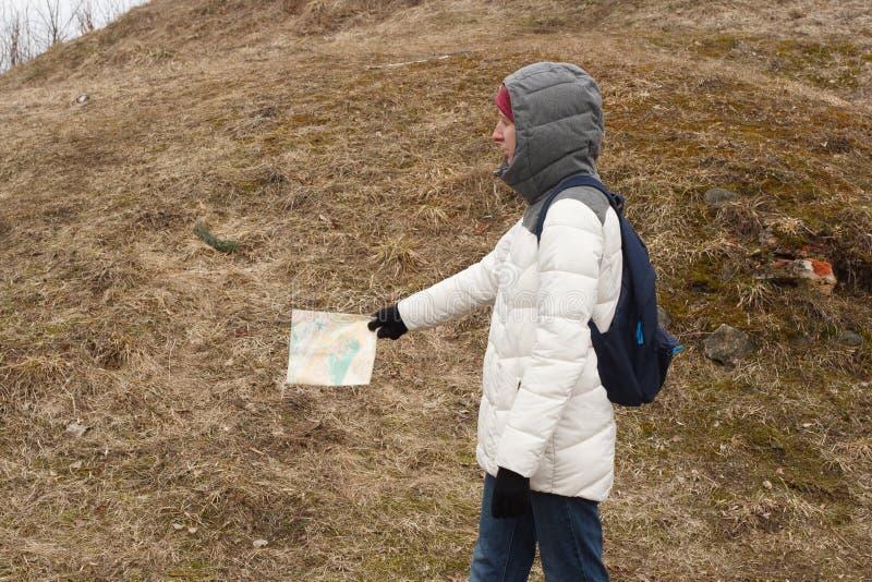 Turista de la mujer joven que mira el mapa en el fondo del parque nacional imagen de archivo libre de regalías