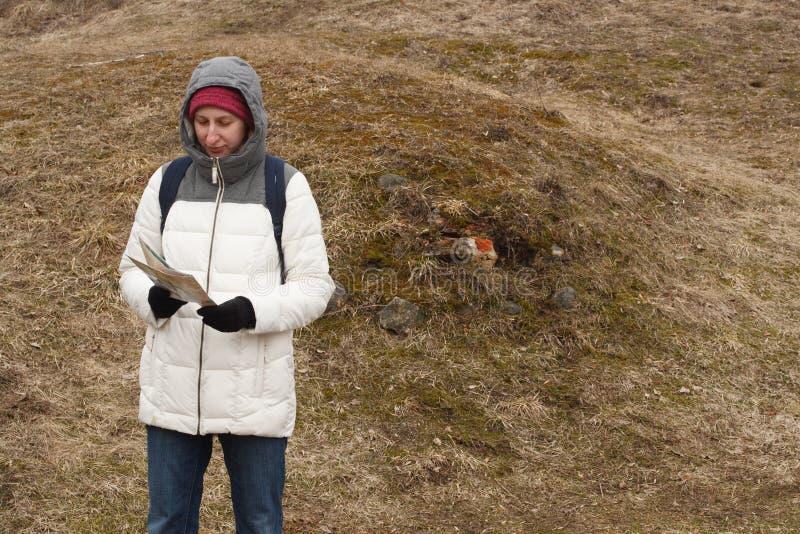Turista de la mujer joven que mira el mapa en el fondo del parque nacional foto de archivo