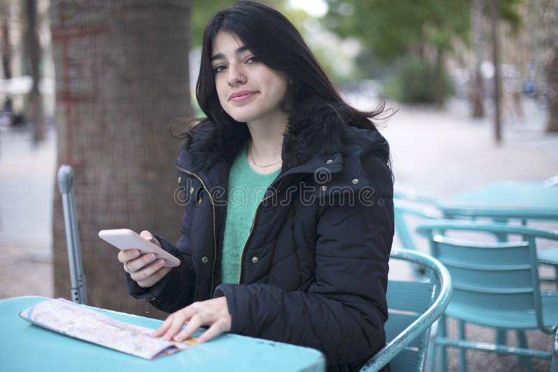 Turista de la mujer joven que se sienta en un café al aire libre, usando el smartphone, sosteniendo el mapa del destino fotos de archivo