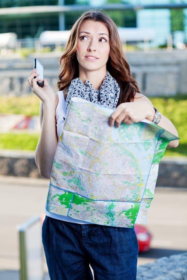 Turista de la mujer joven que sostiene el mapa de papel fotos de archivo