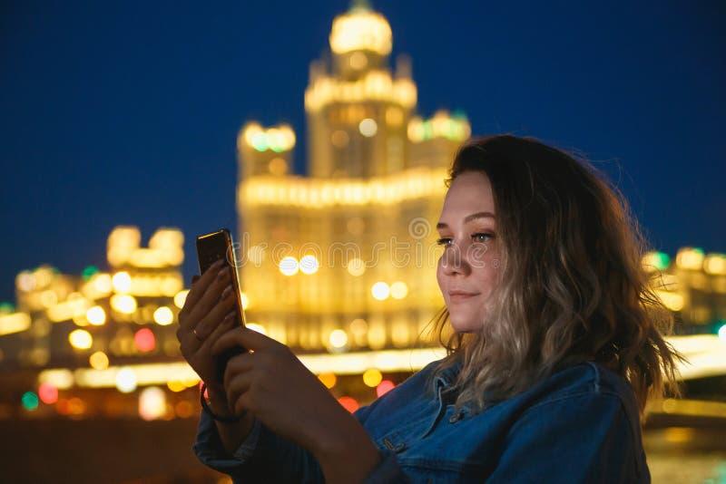 Turista de la mujer que toma imágenes en el teléfono móvil durante el viaje en Moscú Iluminaci?n de tarde Viaje al concepto de Ru foto de archivo