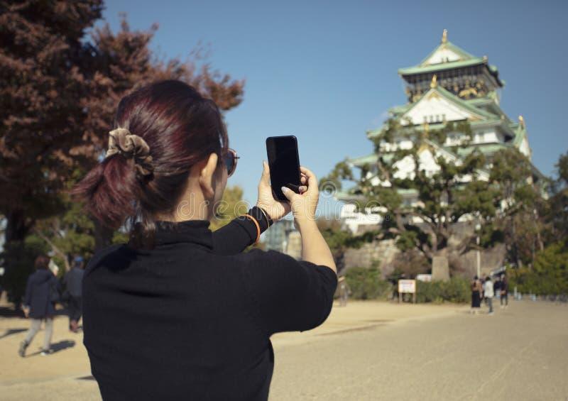 Turista de la mujer que toma una foto del castillo de Osaka por el teléfono elegante, osak imagenes de archivo