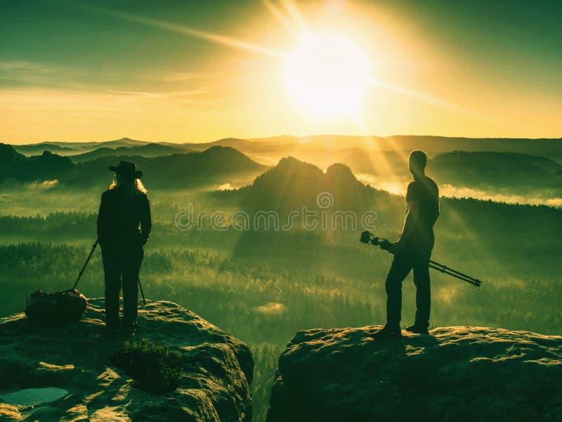 Turista de los pares con la cámara de la foto en la parte superior de la puesta del sol del reloj de la montaña stock de ilustración