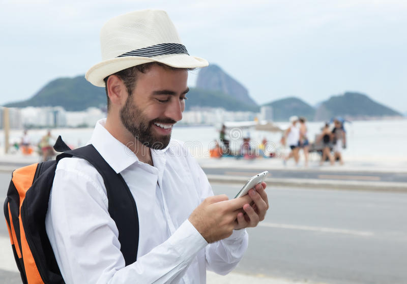 Turista de risa que busca la manera correcta en el teléfono imagen de archivo libre de regalías