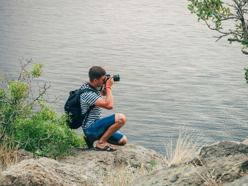 Turista del fotógrafo que toma las imágenes que se sientan en el paisaje marino fotos de archivo