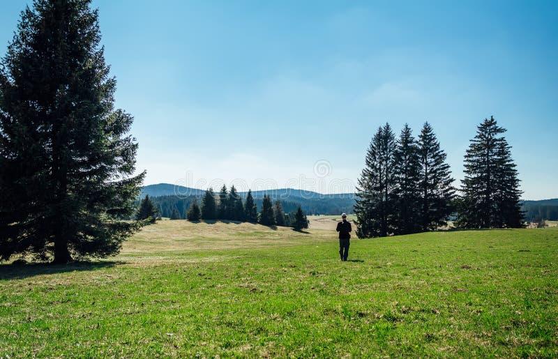 Turista del giovane con lo zaino e la passeggiata bianca del cappuccio nel paesaggio ceco con gli alberi ed il cielo blu fotografie stock libere da diritti