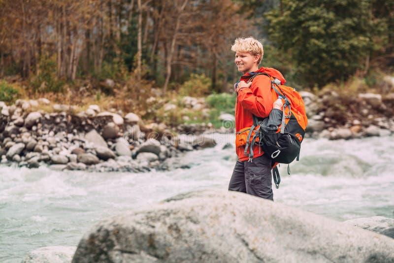 Turista del giovane nella foresta della montagna sulla sponda del fiume fotografia stock