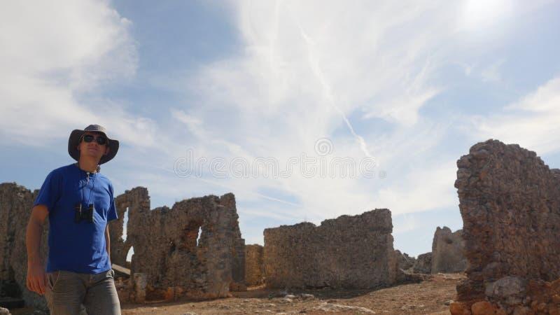Turista del hombre joven con los prismáticos que explora la ciudad antigua imagen de archivo