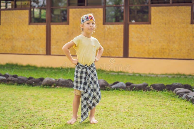 Turista del muchacho en los sarong, ropa nacional del Balinese foto de archivo
