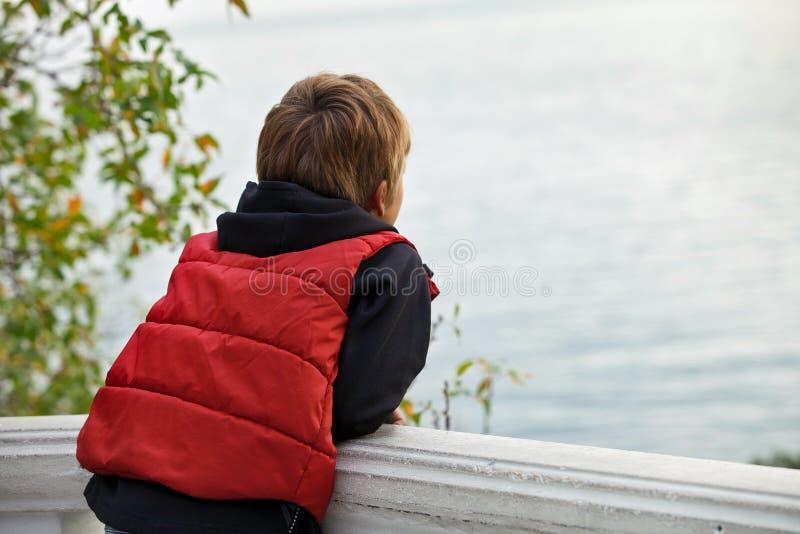 Turista del ragazzo che esamina vago la distanza con il suo di nuovo alla macchina fotografica fotografia stock libera da diritti
