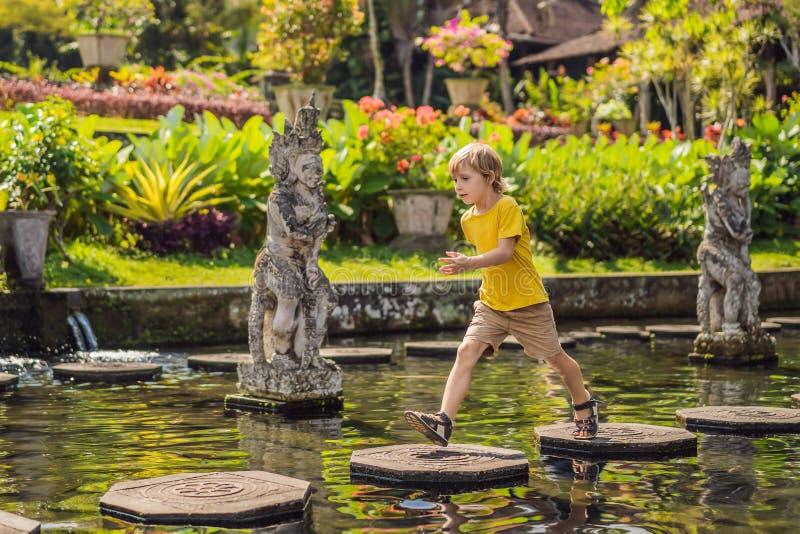 Turista del ragazzo in Taman Tirtagangga, palazzo dell'acqua, parco dell'acqua, Bali Indonesia Viaggiando con il concetto dei bam fotografie stock