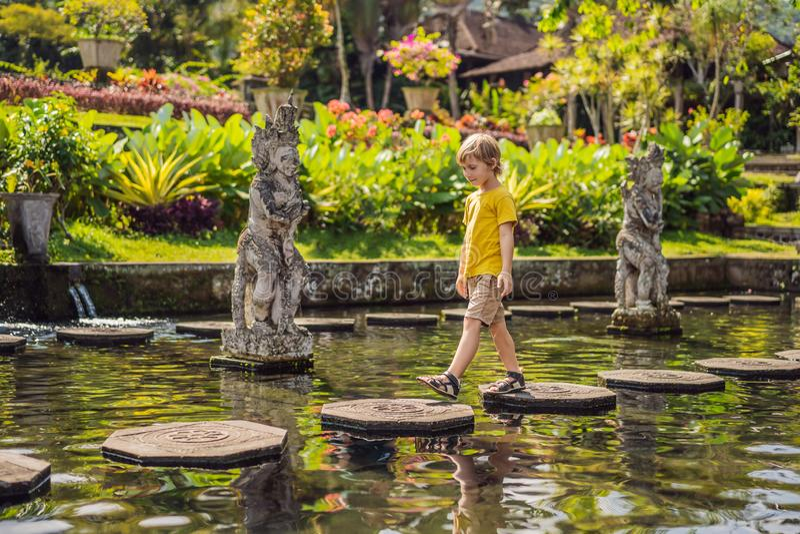 Turista del ragazzo in Taman Tirtagangga, palazzo dell'acqua, parco dell'acqua, Bali Indonesia Viaggiando con il concetto dei bam fotografie stock libere da diritti