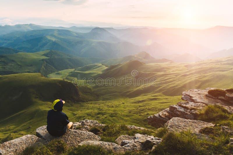Turista dell'uomo di viaggio che si siede da solo sulle montagne del bordo sopra il paesaggio verde di vacanze estreme di stile d immagine stock libera da diritti