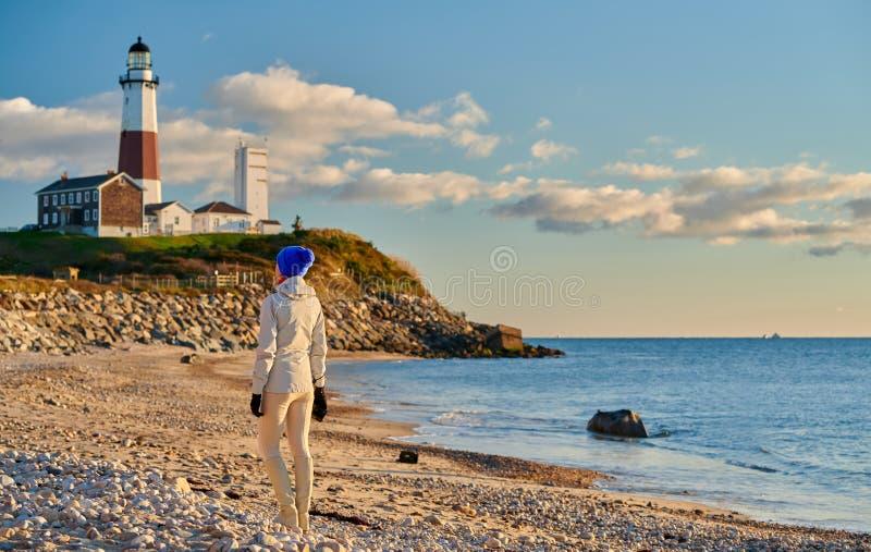 Turista della donna alla spiaggia vicino al faro di Montauk fotografia stock libera da diritti