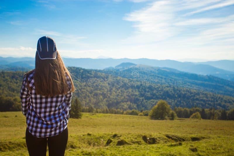 Turista della donna in cappuccio sopra la collina che gode della vista delle montagne fotografie stock