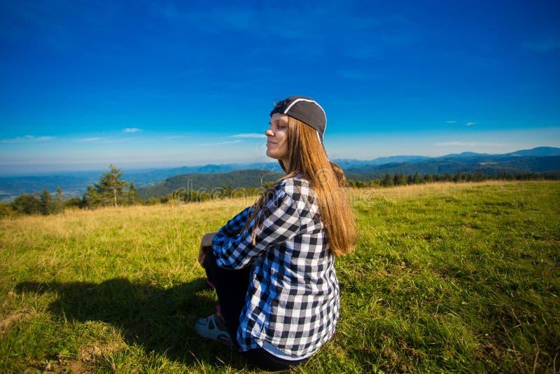 Turista della donna in cappuccio sopra la collina che gode della vista delle montagne fotografia stock