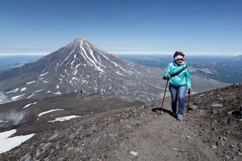 Turista della donna che fa un'escursione e che scala alla cima del vulcano fotografia stock libera da diritti