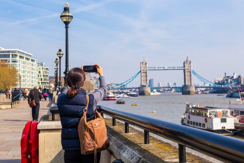 Turista della donna che prende foto sul ponte della torre con la macchina fotografica del telefono cellulare fotografia stock